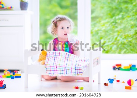 Cute curly toddler girl in a colorful dress feeding her toy bear in a white crib playing in a sunny bedroom with big garden view windows