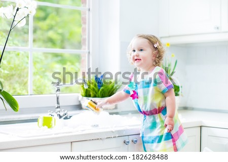 Cute curly toddler girl in a colorful dress washing dishes, cleaning with a sponge and playing with foam in the sink in a beautiful sunny white kitchen with a garden view window in a modern home