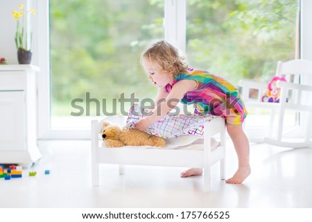 Cute curly toddler girl playing with her teddy bear in a sunny bedroom with big garden view windows
