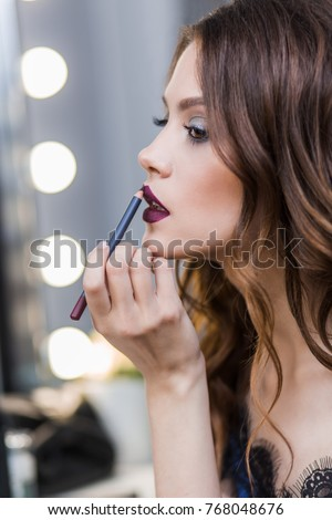 Cute cute girl in a blue dress painted at the mirror, putting on lip pencil professional makeup, makeup, profile, close-up