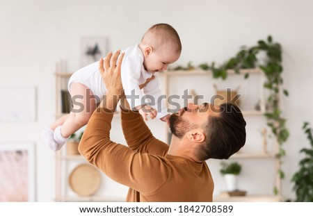 Cute Daddy Playing With Newborn Baby Daughter Cuddling And Bonding Holding Little Toddler In Arms Standing At Home. Father's Love, Parenting And Fatherhood Happiness Concept Foto d'archivio ©