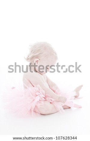 Cute dainty caucasian baby girl with soft blond hair sitting in pink tutu and naked on top looking down and holding her pretty dress