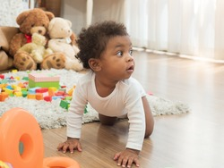 Cute dark skinned little African boy with curly hair crawling around the room, full of teddy bears and colorful toys, looking to his left side.