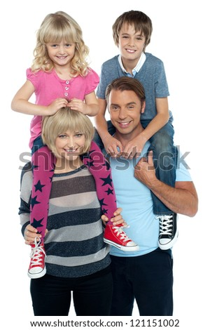 Cute daughter and son riding on their parent's shoulders. All on white background.