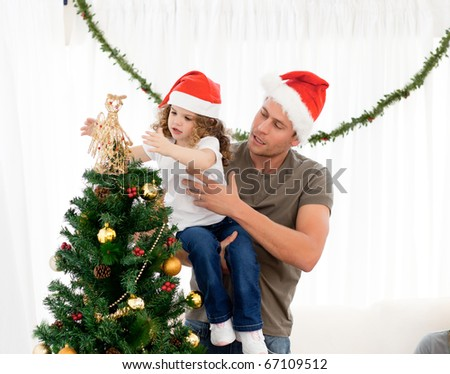Cute daughter decorating the christmas tree with his father in the living room