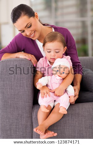 cute daughter hugging a doll at home with mother