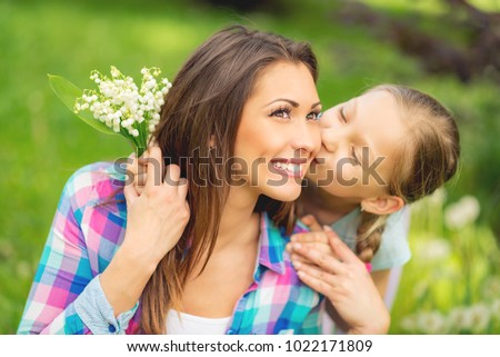 Cute daughter kissing her happy mom and giving to her bouquet lily of the valley for Mother's Day in the nature.