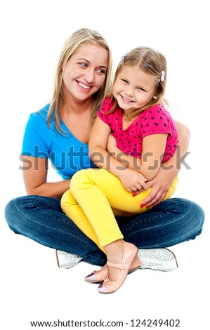 Cute daughter sitting in mother's lap isolated over white