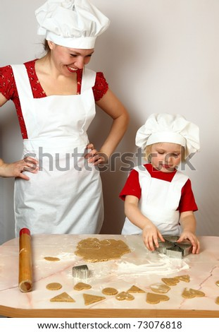 cute daughter with mother in white aprons on kitchen