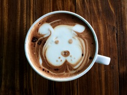 Cute dog face latte art coffee in white cup on wooden table ; cute dog latte art in your cup , love dog love coffee. animal latte art