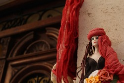 Cute doll of a woman in a red shawl hanging next to an ornate mediterranean front door in Chania, Crete, Greece