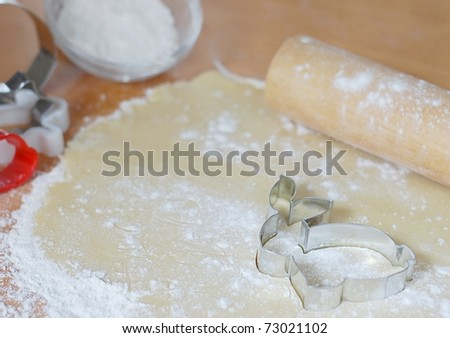 Cute Easter Bunny Rabbit Cookie Cutter on Freshly Rolled Dough with Rolling Pin and Utensils in the Background - stock photo