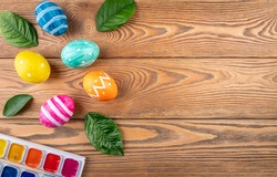 Cute Easter eggs decorated handmade with paint and paintbrush on a wooden background with green young leaves. Copy space.