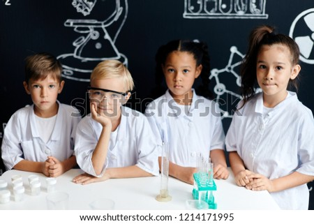 Cute elementary schoolkids looking at camera while standing at desk at chemical labaratory. Young scientists making experiments in school laboratory. Child and science. Education concept. #1214171995