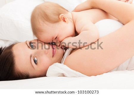 cute embracing mother with baby in bed enjoying time together