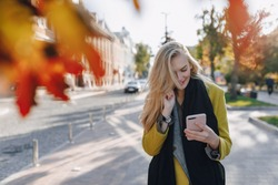 cute emotional attractive blonde woman in coat with smartphone walks the city street. communication during the walk, lifestyle, street in good weather.