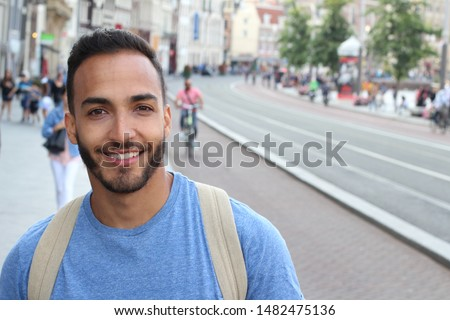 Cute ethnic bearded man smiling outdoors