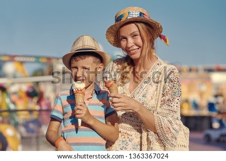 Cute European boy and his mother are walking around the amusement park and eating tasty ice-cream. #1363367024