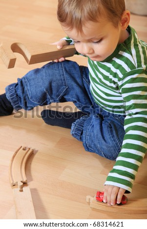 Cute european toddler playing with toy train in kindergarten.