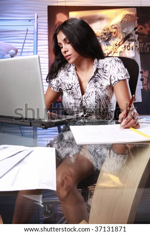 Cute executive in summer attire at her office desk