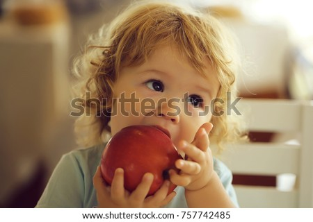 Cute fair-haired blond hazel-eyed kid little child baby boy biting and eating big red apple fruit portrait on blurred background, horizontal picture
