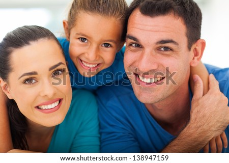 cute family of three face closeup portrait at home