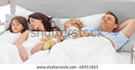 Cute family sleeping together in the parents's bed