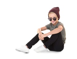 Cute fashionable boy sitting on white background