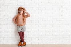 Cute fashionable girl on near white brick wall
