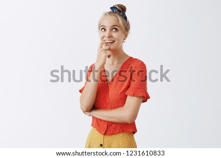 Cute fashionable woman imaging what her life would be if she married. Portrait of joyful dreamy girl with blond hair in vintage polka-dot blouse, biting finger and gazing up with happy smile