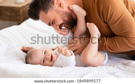 Cute Father Cuddling Bonding With Little Baby Daughter Spending Time Together Lying On Bed At Home. Loving Daddy Laughing Playing With Toddler. Fatherhood, Dad's Love, Child Care And Parenting Joy Foto d'archivio ©