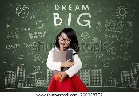 Cute female elementary school student standing in the class while holding a book and apple fruit with Dream Big text on Blackboard