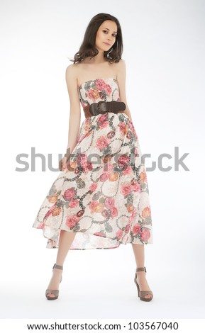 Cute female fashion model posing in prom dress against white background