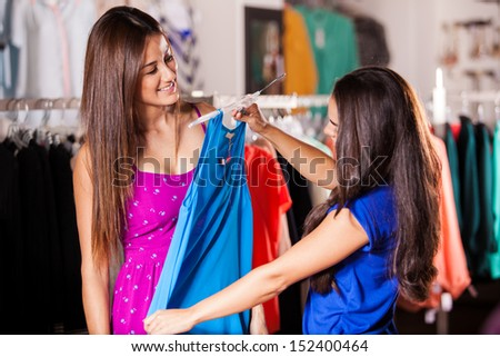 Cute female friends doing some shopping in a clothing store