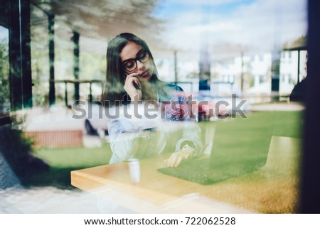 Cute female manager in optical spectacles talking via telephone while working at modern computer and checking online database.Attractive copywriter in eyeglasses communicating via smartphone