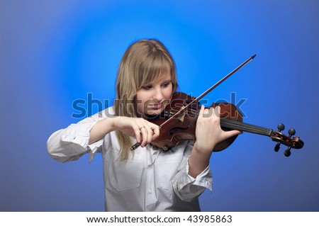 Cute female violinist playing on the violin with blue background