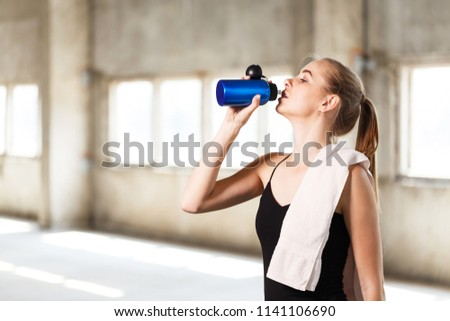Stock Photo Cute fitness blonde girl relaxing and drinking water after a workout at the loft gym