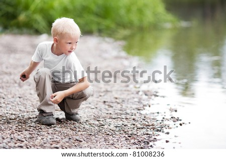cute five year old boy throwing stones to the water outdoor on a summer day