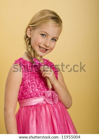 stock photo : Cute five year old girl in a pink princess dress, yellow background.