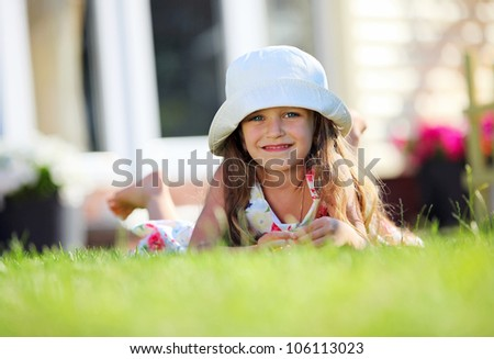 Cute four-year girl lying on the grass outside