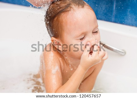 Cute four year old girl taking a relaxing bath with foam. The symbol of purity and hygiene education.