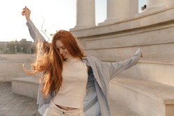 Cute foxy lady dancing outdoors at sunny day. Adorable young long-haired girl , wearing light turtleneck, blue shirt, moving and looking down against city landmark background