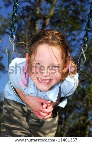 Cute freckle faced tomboy girl on swing outside at park
