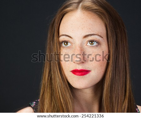 Cute freckled girl on a gray background. #254221336
