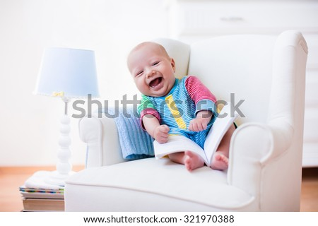 Cute funny baby boy reading a book sitting in a white chair at home. Children read books in a library seat. Nursery and playroom interior for kids. Early development and learning for young kid. stock photo