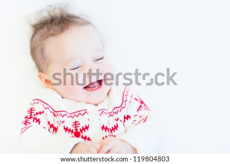 Cute funny baby girl laughing wearing a knitted snowflake sweater