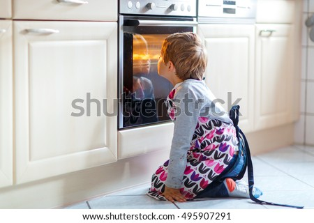 Cute funny blond kid boy baking muffins in domestic kitchen. Child having fun with helping, sitting near ofen and waiting for cupcakes.