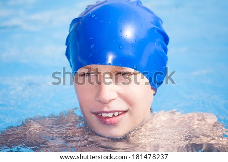 Cute funny child in a swimmer cap swimming in a sunny pool