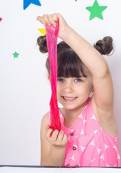 Cute funny girl play with slime. Kid squeeze and stretching toy slime.