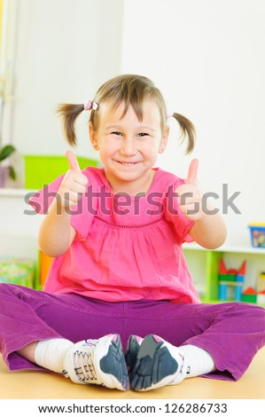 Cute funny girl showing thumbs up and smiling